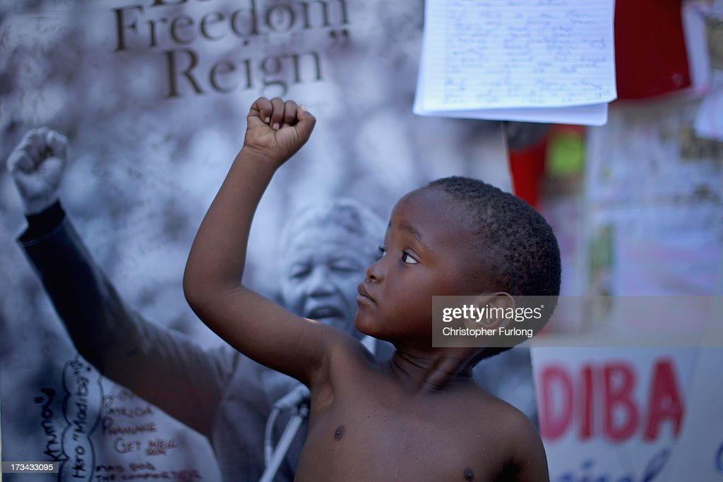A young boy, a member of the Maitibolo Cultural Dance Troop, pays his respects to Former South African President Nelson Mandela at the tribute wall outside the Medi-Clinic Heart Hospital on July 14, 2013 in Pretoria, South Africa. Anti-apartheid icon Mandela has been hospitalized at the Medi-Clinic Hospital since June 8 for treatment for a recurring lung infection. His wife Graca Machel has said she was less anxious about his condition five weeks after he was first admitted.