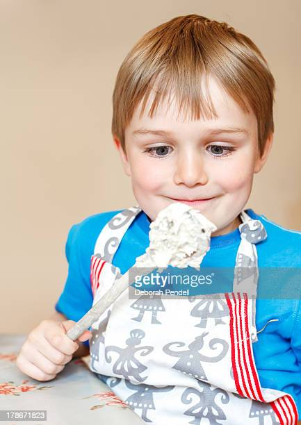 A young boy about the lick the mixing spoon