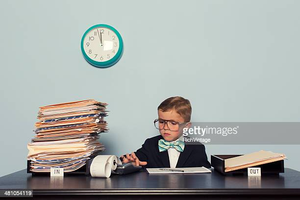 Young Boy Accountant Crunches Number at the Office