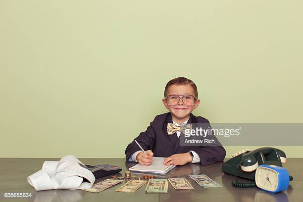 young boy accountant records taxes to be paid - calculator stock photos and pictures
