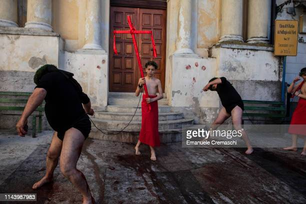 A young boy acting as Acciommu stands between two flagellants scourging themselves on April 20 2019 in Nocera Terinese Italy The Rite of Vattienti...