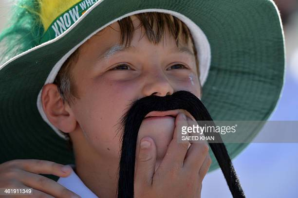 A young boy adjusts his artificial moustache during the first one day international cricket match of the series between Australia and England in...
