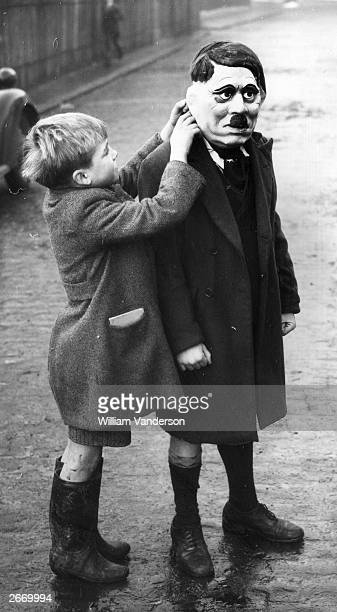 A young boy adjusts his friend's Adolf Hitler mask during a game on a street in King's Cross London