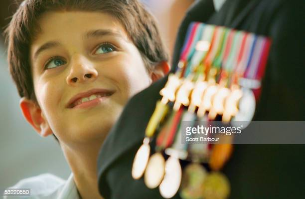 Young boy admires a war veterans medals near Buckingham Palace on National Commemoration Day July 10, 2005 in London. Poppies were dropped from the...