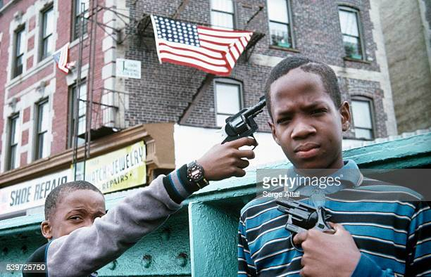 A young boy aims a fake gun to his friend's temple in the streets of New York City