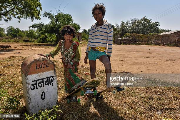 Young boy and a girl pose with their skateboards near Zero milestone of village on October 26, 2016 in Janwaar, India. Thanks to a German community...
