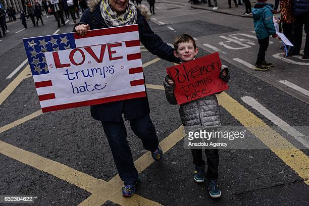 A young boy and a woman hold placards during a protest held in solidarity with the Washington DC Women's March in Dublin Ireland on January 21 2017
