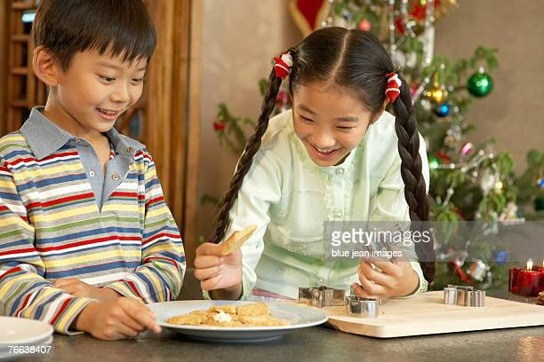 a young boy and a young girl make christmas cookies together. - zakelijke kleding stock pictures, royalty-free photos & images