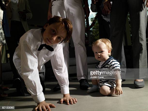 Young Boy and baby sitting on floor