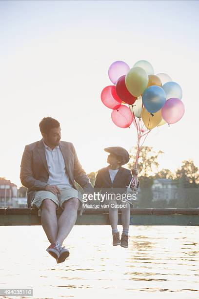 Young Boy and Father on a Pier with Balloons