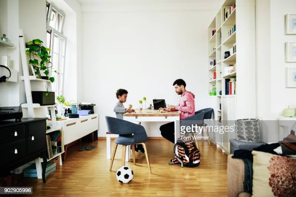 Young Boy And Father Playing Game Together At Home