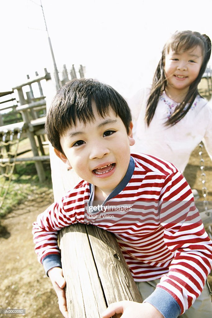 Young Boy and Girl at an Adventure Playground : Stock Photo