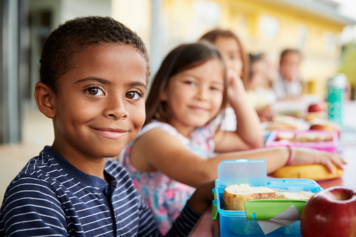 Young boy and girl at school lunch table smiling to camera 1031380420