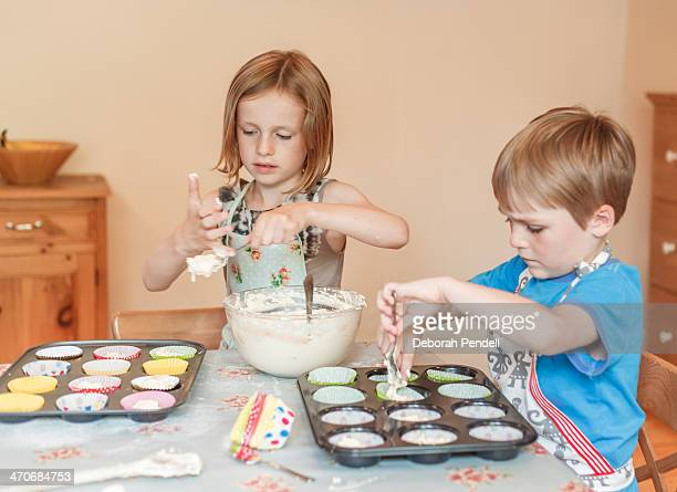 Young boy and girl baking cakes