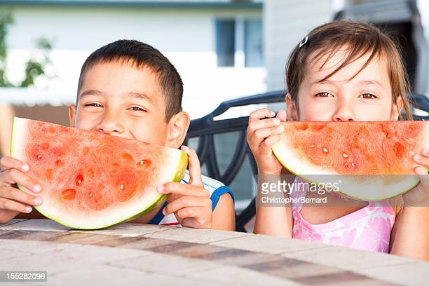 Young boy and girl eating watermelon outdoors