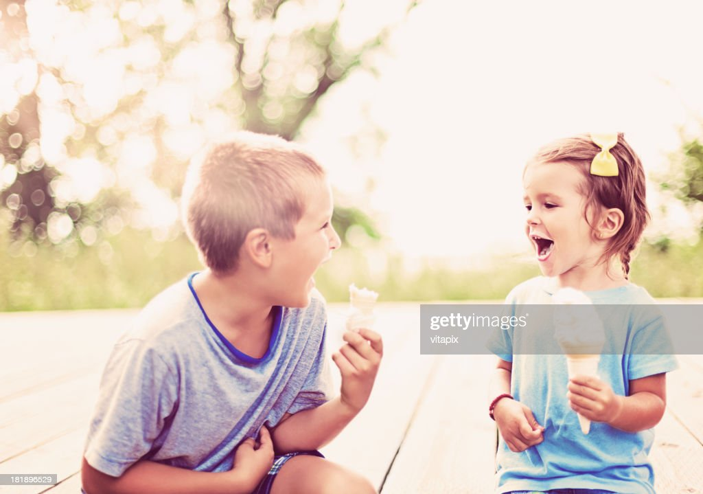Young boy and girl enjoying ice cream on a summer day : Stock Photo