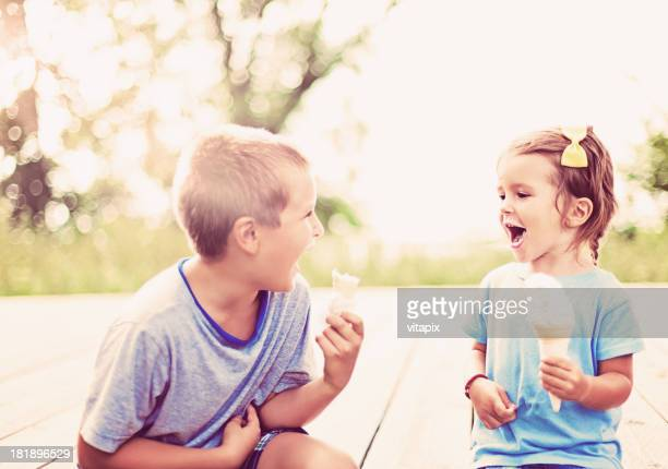 Young boy and girl enjoying ice cream on a summer day