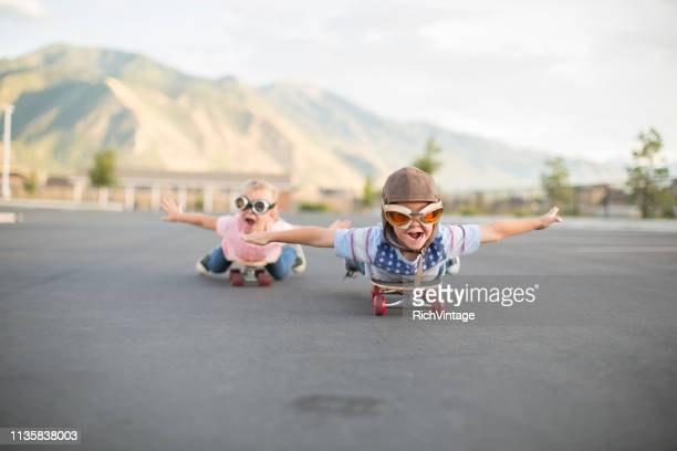 young boy and girl flying on skateboards - vintage airplane stock pictures, royalty-free photos & images