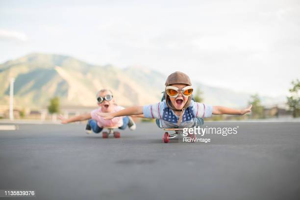 young boy and girl flying on skateboards - courage stock pictures, royalty-free photos & images