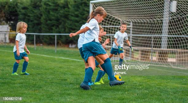 young boy and girl footballers playing practice match - soccer competition stock pictures, royalty-free photos & images