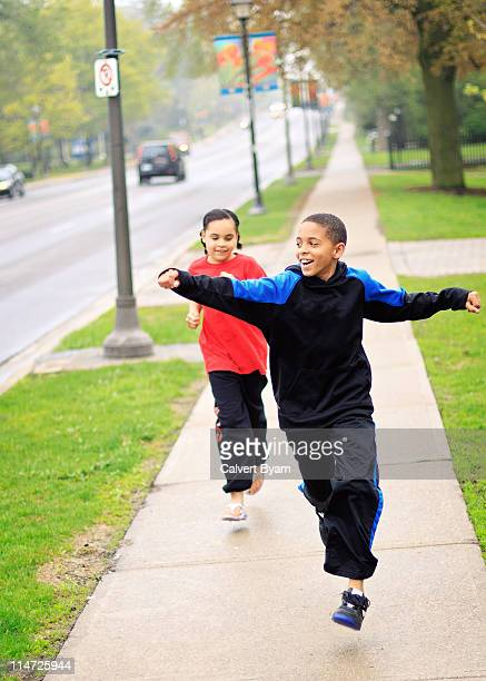 Young boy and girl having foot race on sidewalk