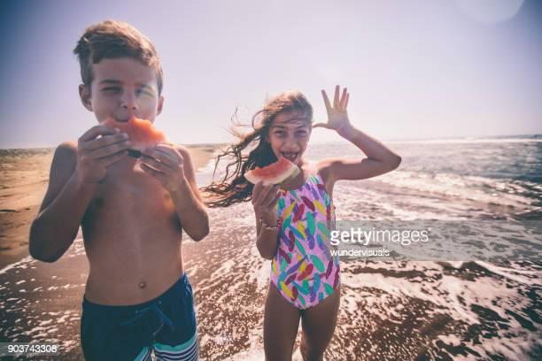 Young boy and girl having fun eating watermelon at beach