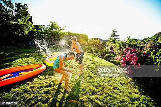 Young boy and girl having water balloon fight