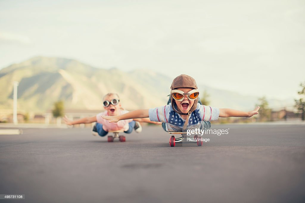 Young Boy and Girl Imagine Flying On Skateboard : Stock Photo