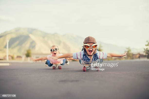 young boy and girl imagine flying on skateboard - vreugde stockfoto's en -beelden
