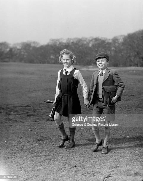 A young boy and girl in school uniform hold hands This photograph was sold to companies in the UK Canada and Belgium Images of children are common in...