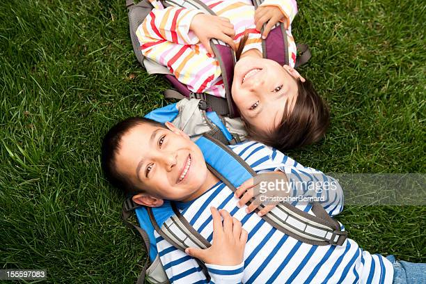 Young boy and girl laying in the grass at school