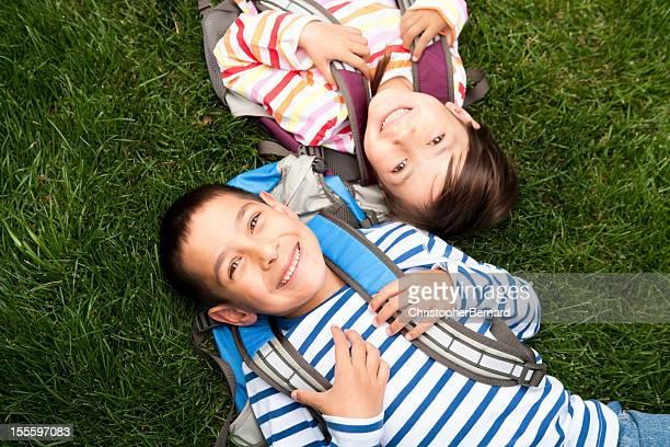 Junge Jungen und Mädchen, die Festlegung auf Gras in der Schule