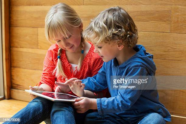 Young boy and girl looking at tablet computer