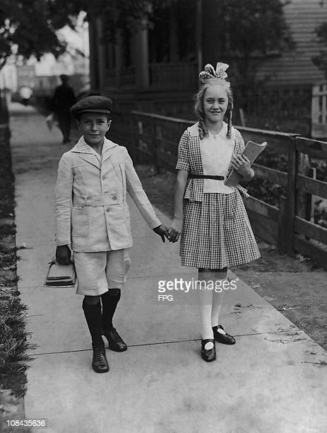 A young boy and girl on the way to school for the first day of a new term circa 1920