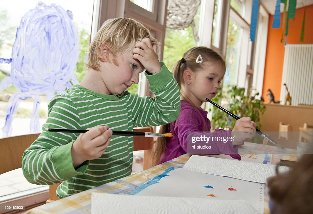 Young boy and girl painting in the kindergarten : Stock-Foto