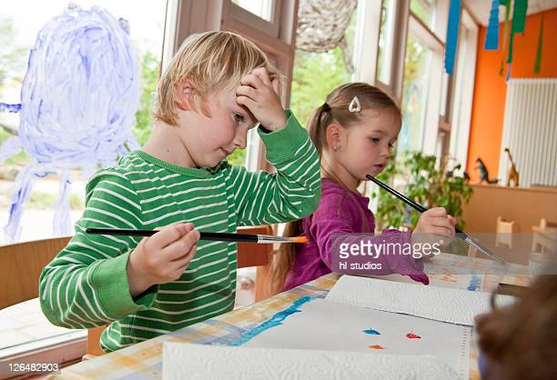 Young boy and girl painting in the kindergarten