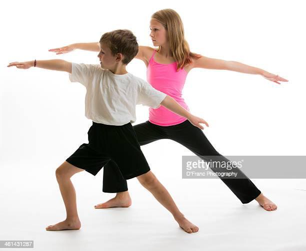 Young boy and girl perform yoga namiste pose