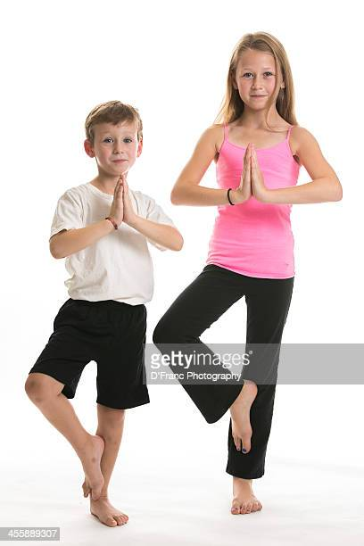 Young boy and girl performing yoga