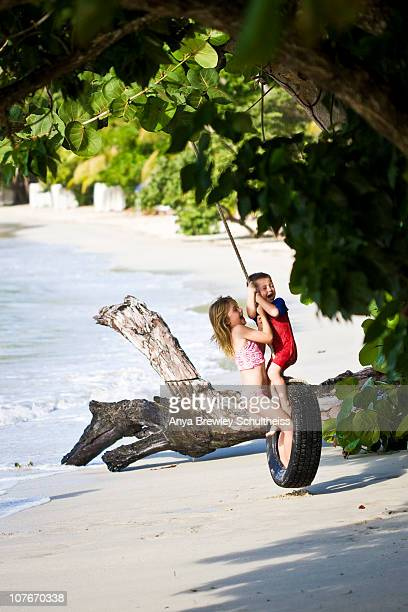 young boy and girl play and laugh on a tire swing - cane garden bay stock pictures, royalty-free photos & images