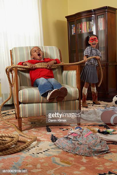 Young boy and girl (6-7 years) playing in messy living room, girl tying boy with rope