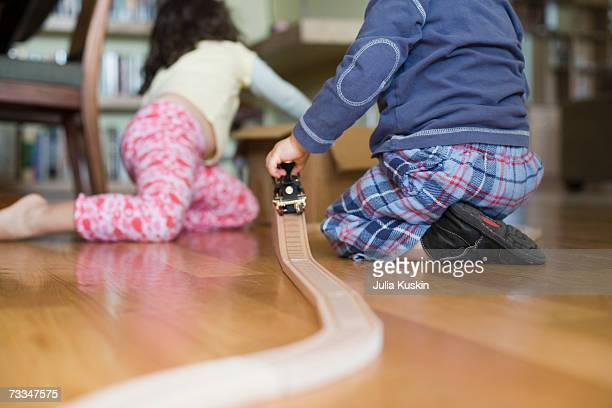 young boy and girl (2-5) playing with toy train on polished floor - parte inferior - fotografias e filmes do acervo