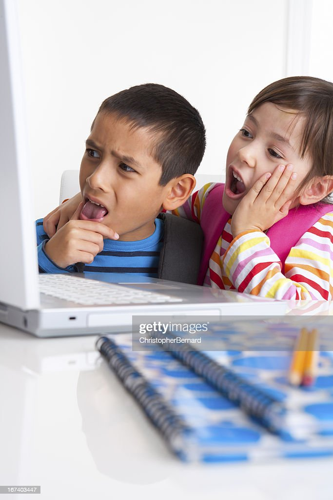 Young boy and girl researching on the internet : Stock Photo