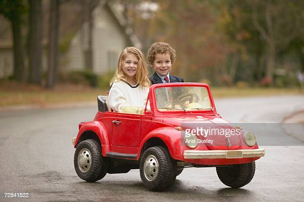 Young boy and girl riding in toy car