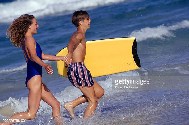 young boy and girl(14-15 years) running in surf, side view - 14 15 years stock pictures, royalty-free photos & images