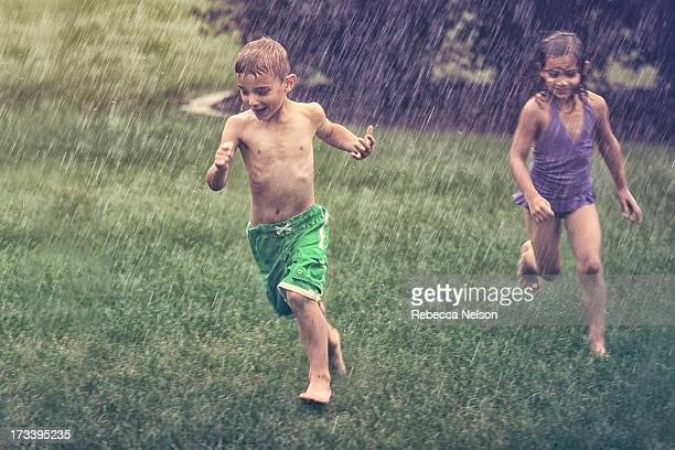 young boy and girl running through rain storm