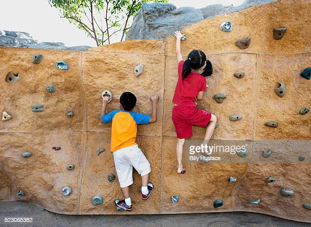 A young boy and girl scaling a climbing wall outdoors in a park.