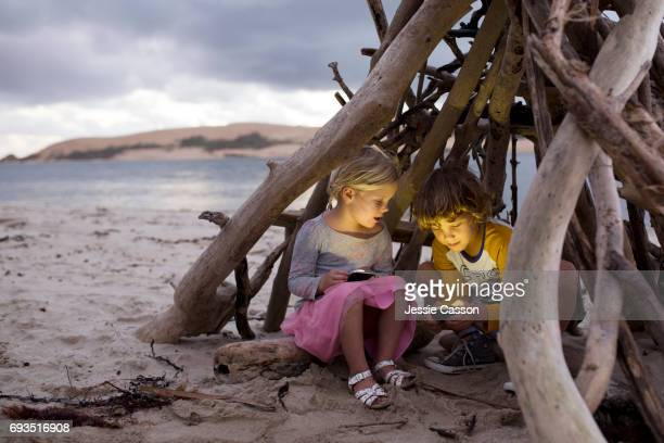 Young boy and girl sit in a homemade driftwood teepee on a beautiful beach on devices/phones