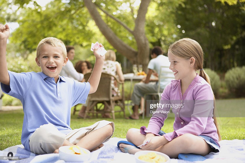 Young Boy and Girl Sit in Their Garden Playing Cards, the Boy Cheering as He Wins the Card Game : Stock Photo