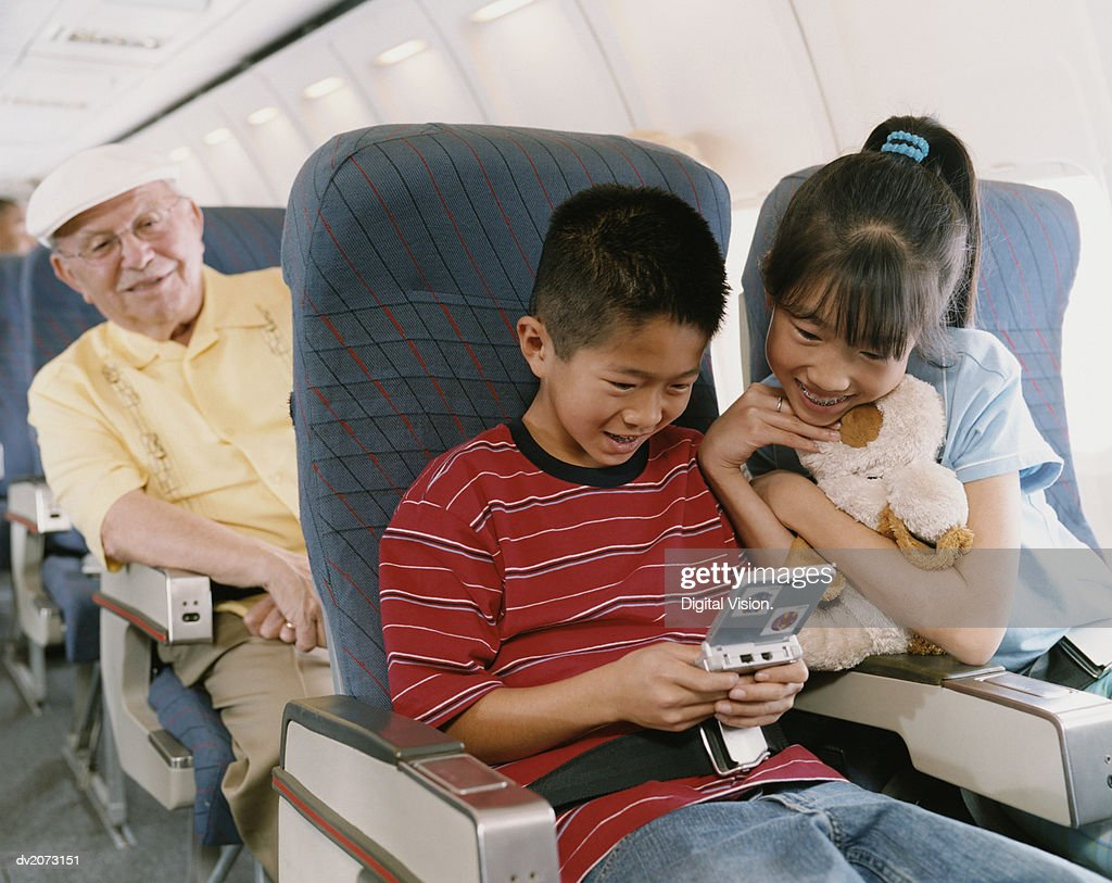 Young Boy and Girl Sit on a Plane Playing a Computer Game : Stock Photo