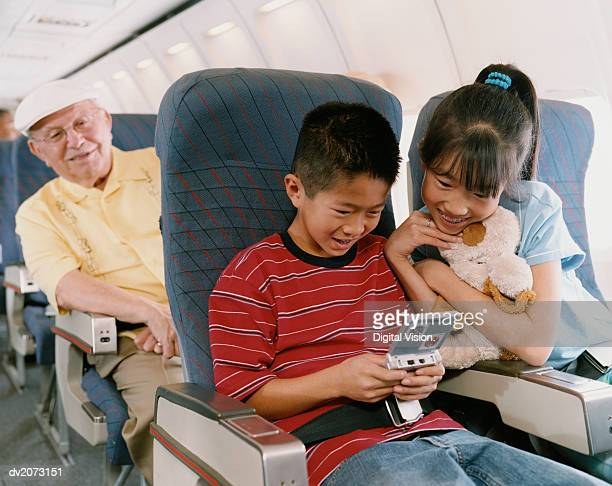 Young Boy and Girl Sit on a Plane Playing a Computer Game